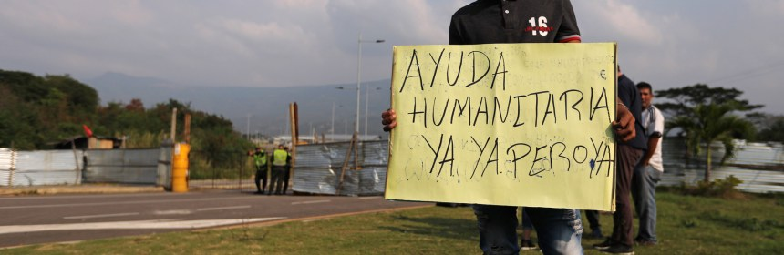 """A Venezuelan man holds a sign that reads """"Humanitarian aid, now"""" in front of the entrance of the Tienditas cross-border bridge, in Cucuta, Colombia February 6, 2019. REUTERS/Luisa Gonzalez"""