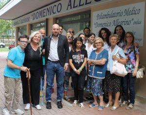 Alessio Vincenzotto al centro a sx Antonella Allegrino e i volontari dell'associazione davanti al poliambulatorio