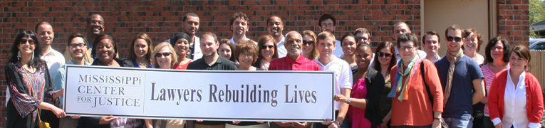 Group photo of students and faculty holding a sign that says Mississippi Center for Justice: Lawyers Rebuilding Lives