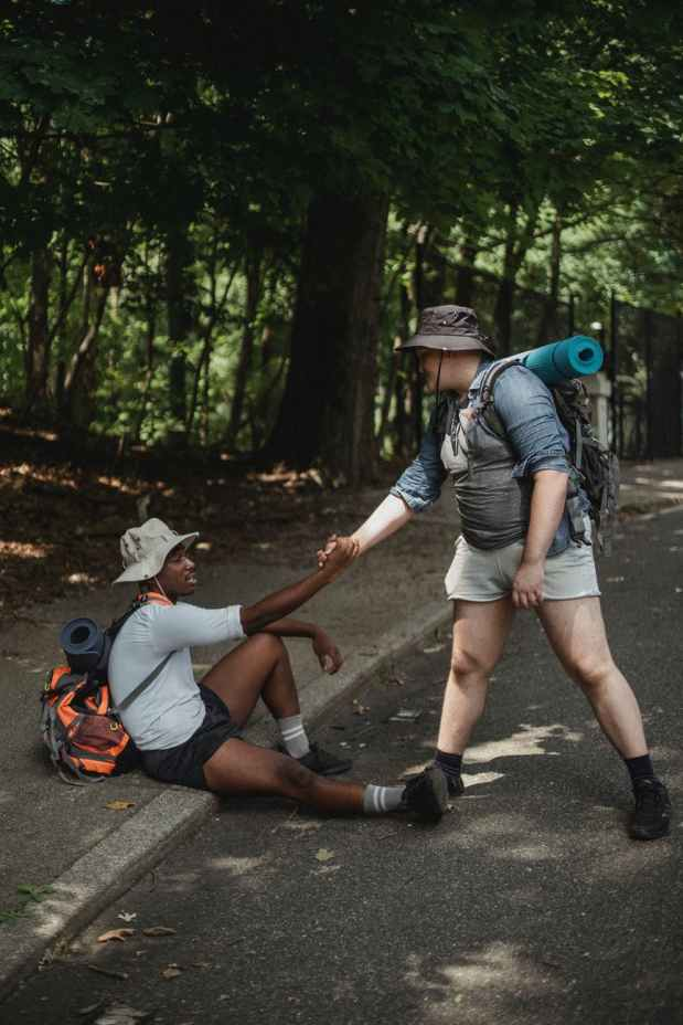 hiker holding hand of black friend on road