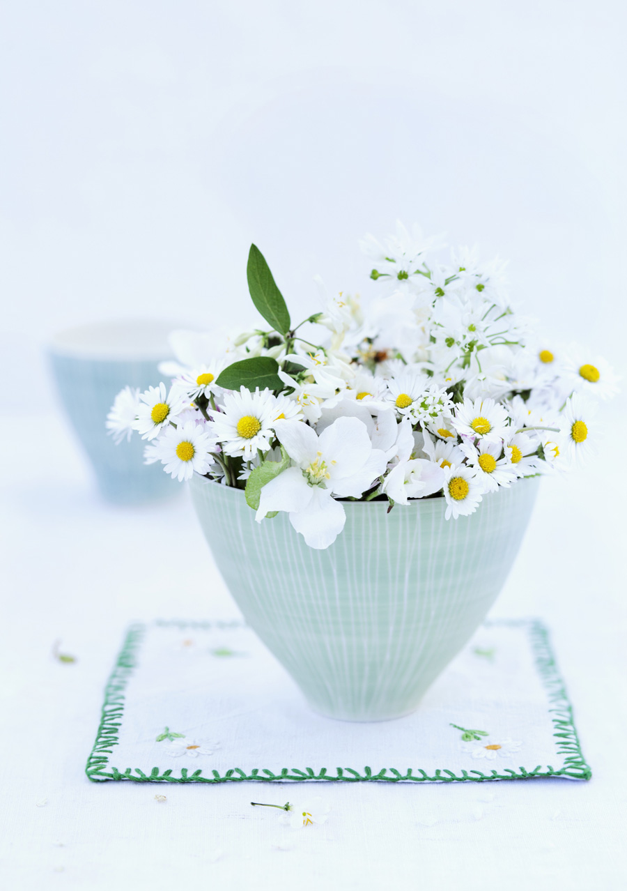 Daisies, apple blossom and sweet woodruff flowers in ceramic bowl on embroidered doily