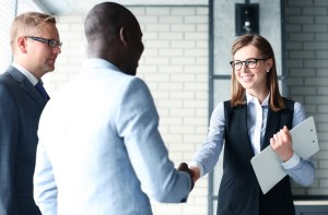 female CEO shakes hands with men