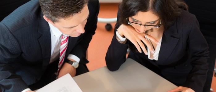 man and women bent over paperwork