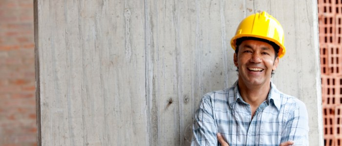 minority construction worker leaning against a wall smiling