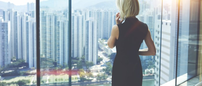 business woman staring out high rise window
