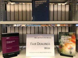 "A book display with three books, on two levels of a bookcase. In the middle is a sign that says ""New and featured books: Fair Dealings Week"". Book titles are in the blog post."