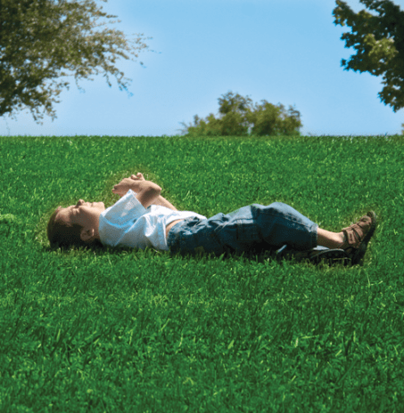 Boy laying in grass yard