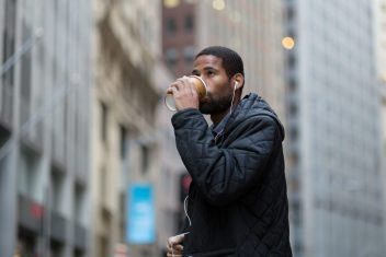 Young male drinking coffee in the city.