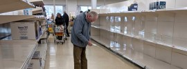 pic of shopper and empty grocery shelves