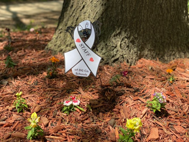 Ribbon supporting staff of Douglas County schools in flowerbed