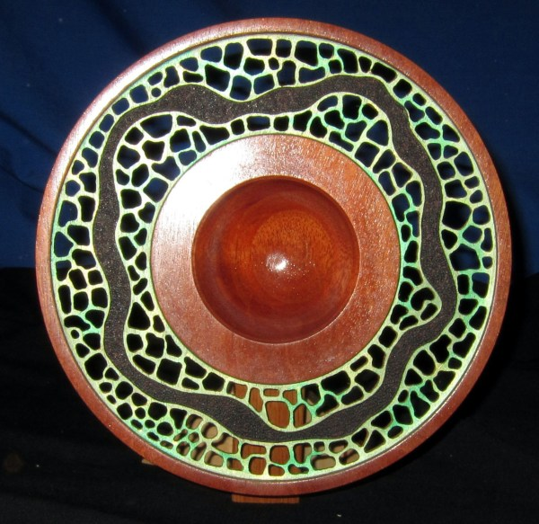 """Dennis Montville, """"Forest Path"""" - This is a turning that is like a plate but with a small cup in the center that also provides the foot to raise it up. It also includes a display stand to hold it as you see in the photo. It is held on the stand by two embedded magnets that align to two more magnets in the stand. It can also be placed flat on a shelf or table. The piece is made of one piece of mahogany that is turned, pierced and painted such that a path is defined as if threading through a forest. Mahogany, piercing, acrylics, 10 x 3, $125"""