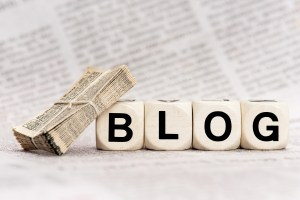 A stack of newspapers and dices spelling out 'Blog'.
