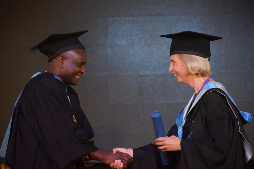 Student Francis Munyao shaking Patricia McKellar's hand at graduation ceremony