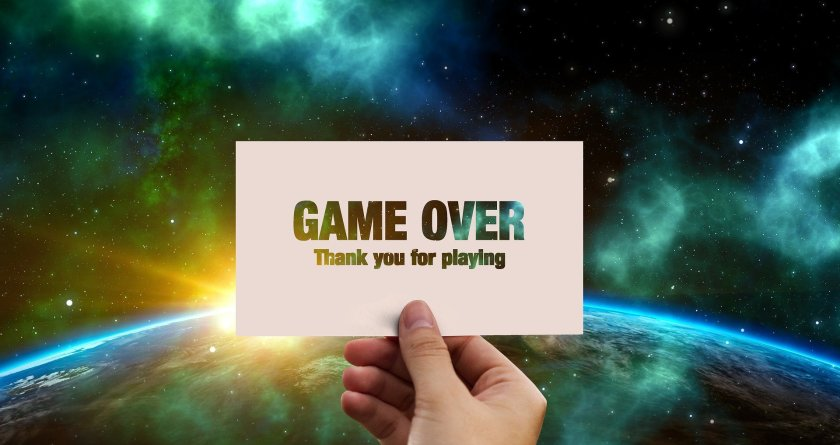 Hand holding a sign 'Game Over - Thank you for playing'.