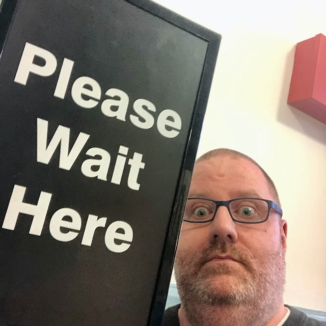 "Kevin sitting by a sign that says ""Please Wait Here"""