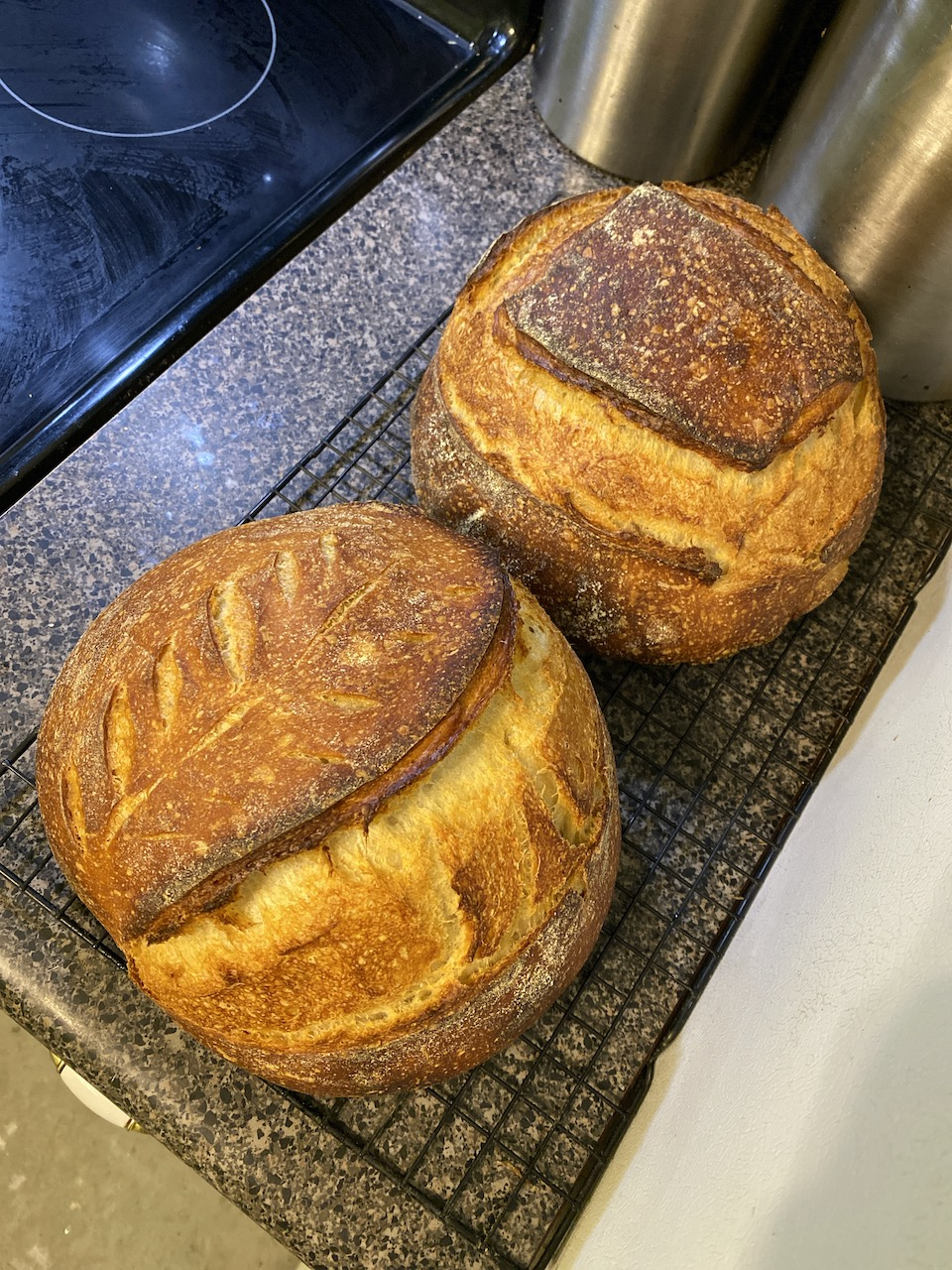 Two gorgeous loaves of pain au levain on a cooling rack.