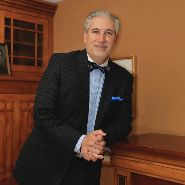 Professional photo of Jeff in suit leaning on credenza