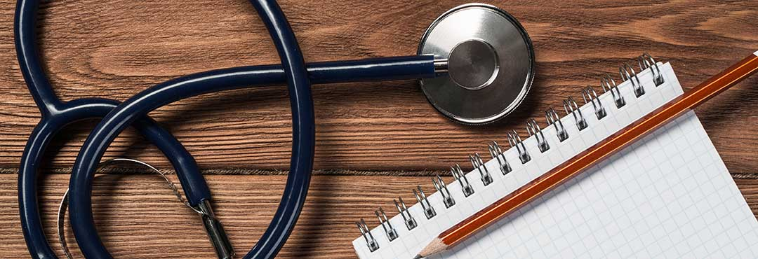 Stethoscope beside pen and paper to denote medical and professional standards that can also be presented evidence.