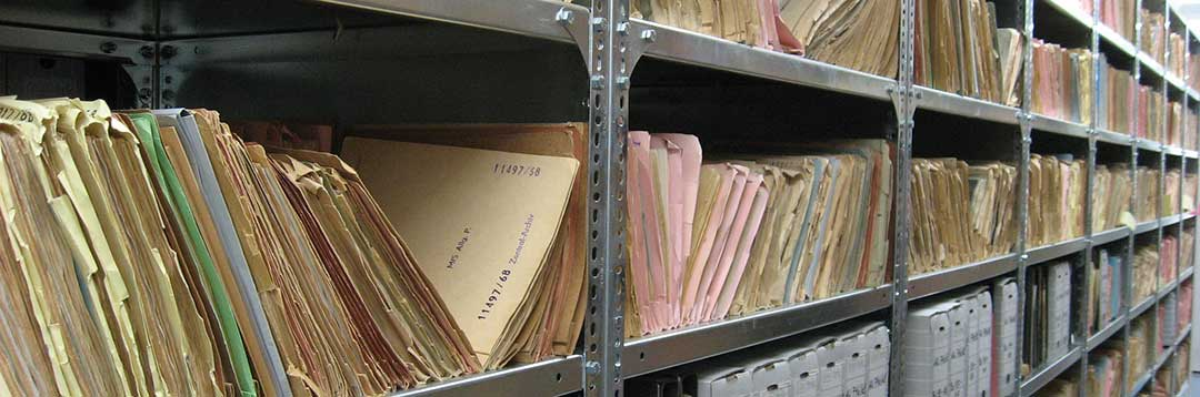 Files on shelving racks to illustrate the need for a thorough and complete inventory.
