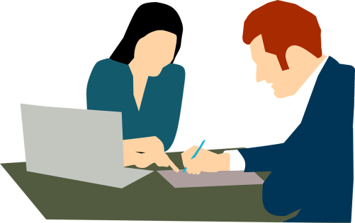 A woman watching as a man signs a will.