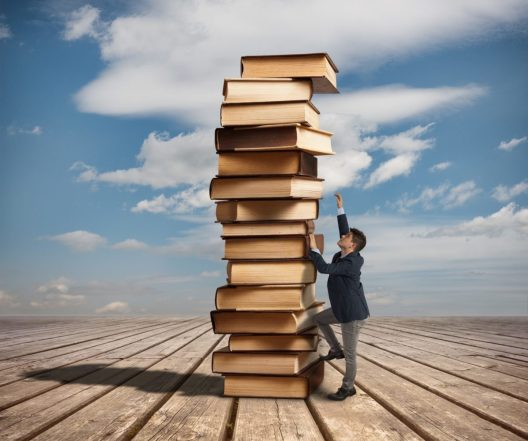 Man climbing a stack of books