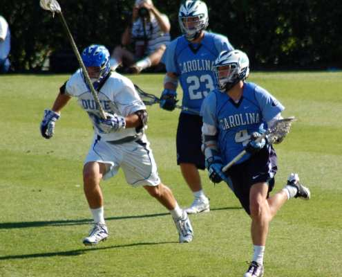 Duke Lacrosse long stick midfielder LSM pursues the NorthCarolina midfielder carrying the ball