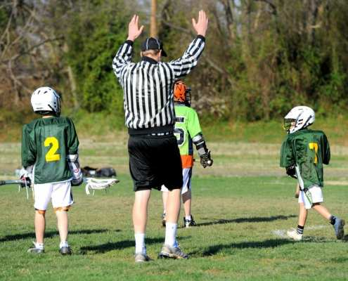 youth lacrosse official signals a goal