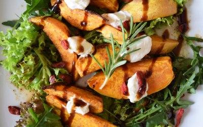 Süßkartoffel-Wedges mit Gojibeeren und Schafkäse auf Salatbeet