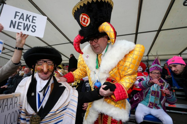 Aalst mayor Christoph D Haese (R) and a Jewish caricature pictured during the yearly carnival parade in the streets of A
