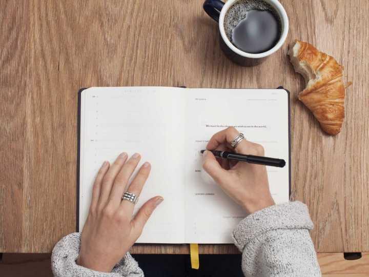 Personne qui écrit dans un carnet avec café et croissant entamé