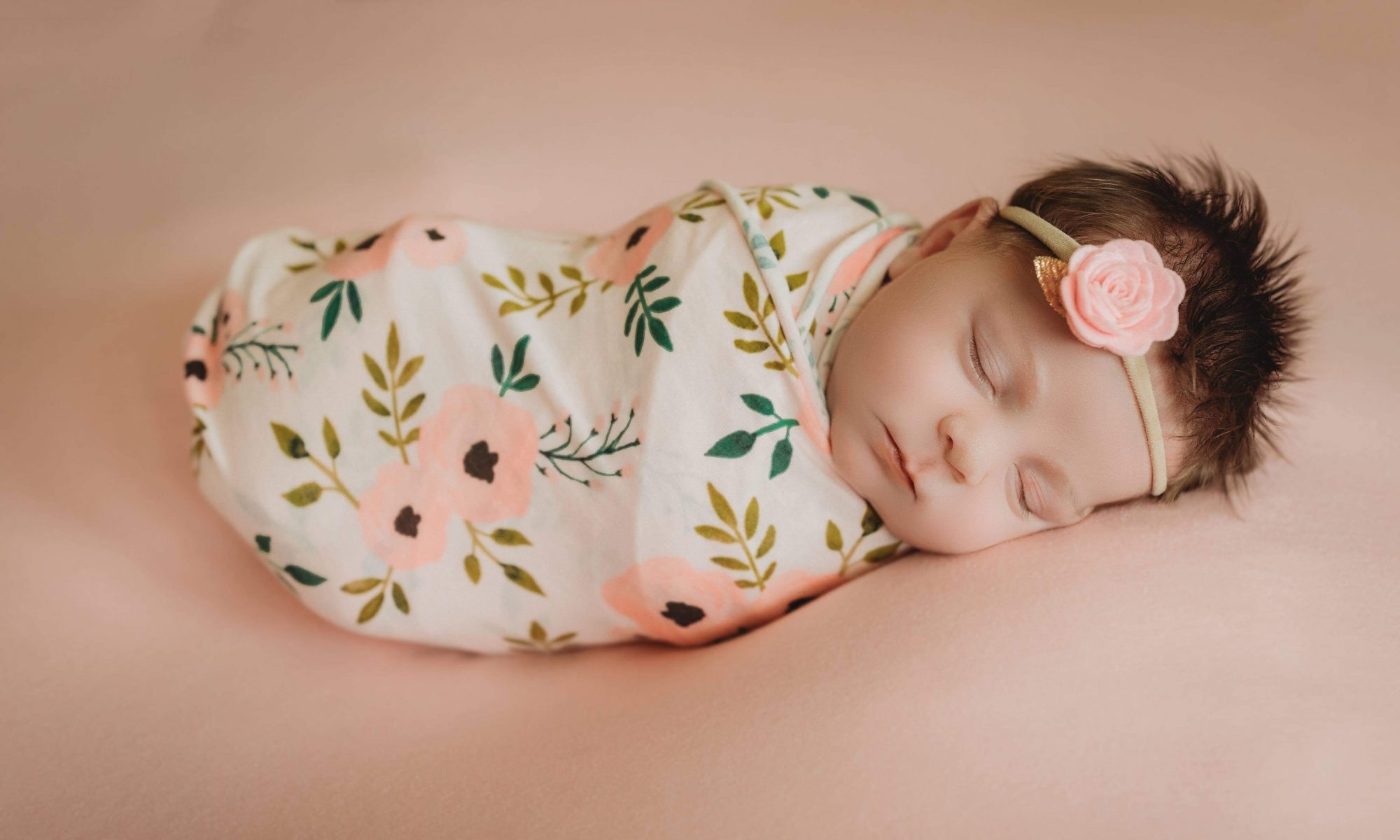 lifestyle newborn photography session with baby girl newborn posed on bed