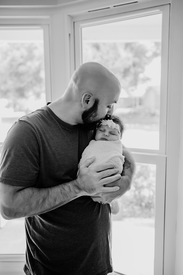 Father kissing his newborn baby girl during tampa newborn photography session. Author is discussing why you should skip hospital baby pictures and book a newborn photographer instead.