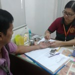 Nililinis ni Ms. Irene Tibor ang daliri ng nagpapa-eksamin.