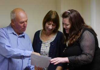 Picture of three people looking at a piece of paper for leadership training