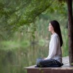 Woman meditates by water