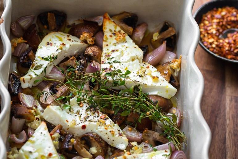 branza feta la cuptor cu ciuperci, ceapa si cimbru intr-o tava si fulgi de chili