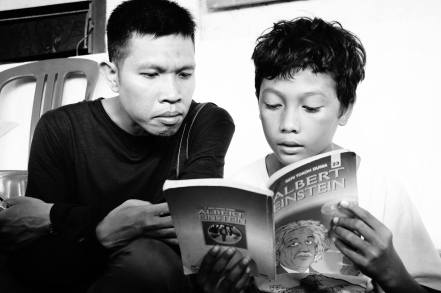 Agus reading with a child at Backpacking Library Project PC: Ziadah