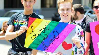 three men holding assorted painted love is love banner