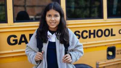happy hispanic girl near school bus