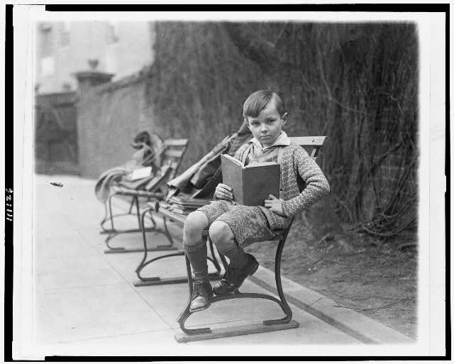[Unidentified boy, seated on park bench, probably in Washington, D.C., holding book]
