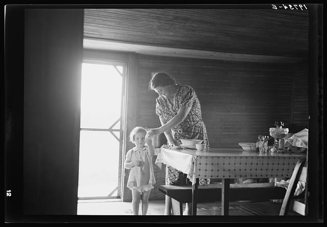 "Wife and child of tobacco sharecropper. The littlest girl comes in from outside for something to eat while mother is doing her housework. The child next to the baby is called in this country the ""knee baby"". Person County, North Carolina"