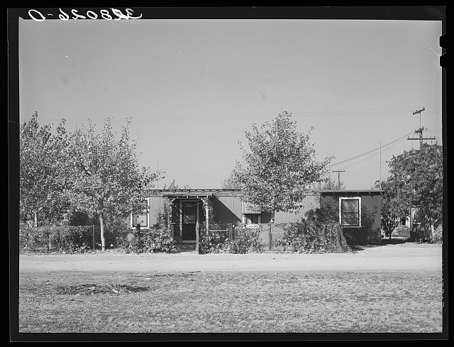 Boxcar homes with covered entrance way, windows, surrounding fences, yard and trees.