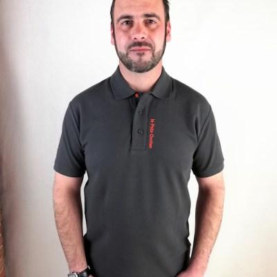 Homme portant un Polo noir avec croix occitane brodée