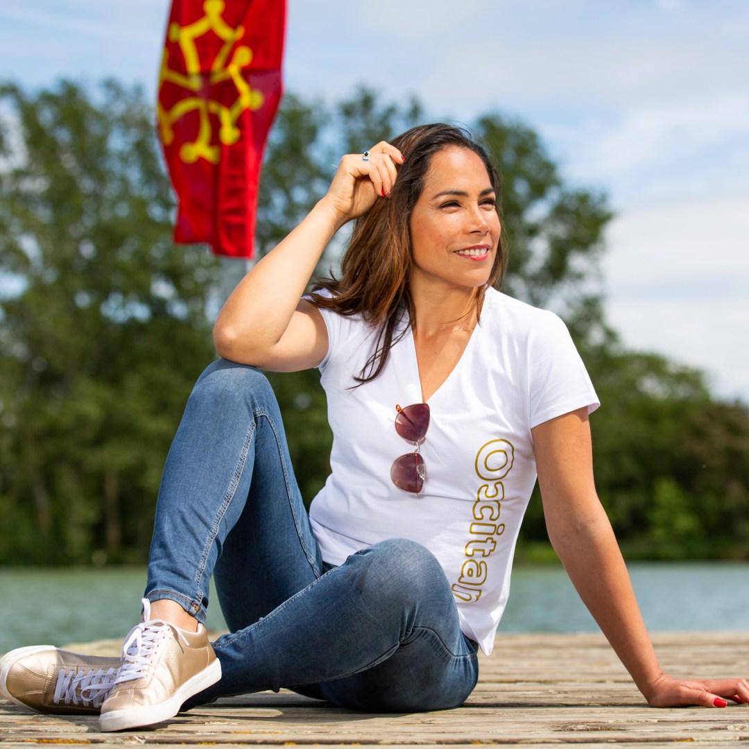 Modèle portant un tee shirt occitan assise près d'un lac