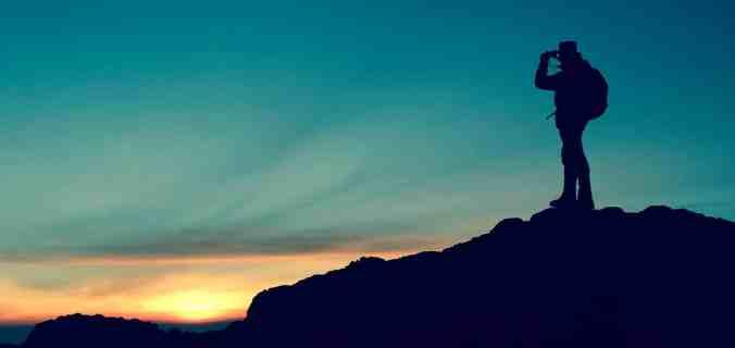 Homme avec des jumelles qui vise le soleil au loin