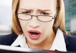 Shocked, surprised business woman sitting in front of laptop