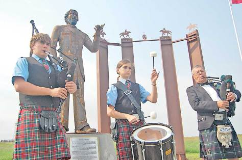 """From left, Thomas Quiring, Elizabeth Quiring and Jim Beebe play during an Aug. 30 ceremony to dedicate a sculpture of Louis Riel, called """"The Invitation."""""""