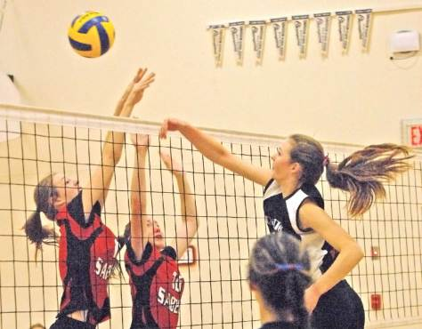 The RaiTec's Tori Rendall (11) sends the ball over the net as the Hanley Sabers' Kirsten Cory (11) and Vanessa Lohrey (10) attempt to block during a conference finals game in Davidson on Nov. 7.