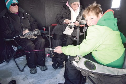 Keeping warm inside this tent shack at the Elbow ice fishing derby on March 11 were, from left, Barb Glubis, Laurie Niska and Jake Glubis.