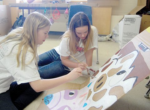 Darrah Langager (left) and Rachel Stamnes paint a cow design as part of a totem pole in the art classroom, one of several stations open to visitors during Leadership Day at Loreburn Central School on Thursday.